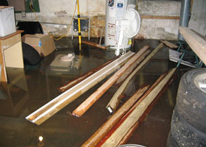 A severely flooding basement in Clearfield, with lumber and personal items floating in a foot of water