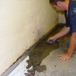 A basement waterproofer installing a perimeter drain system in Coudersport